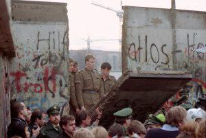 Alcune guardie di confine della Germania Est guardano cadere un pezzo di Muro alla Porta di Brandeburgo, l'11 novembre 1989. (AP Photo/Lionel Cironneau, File)